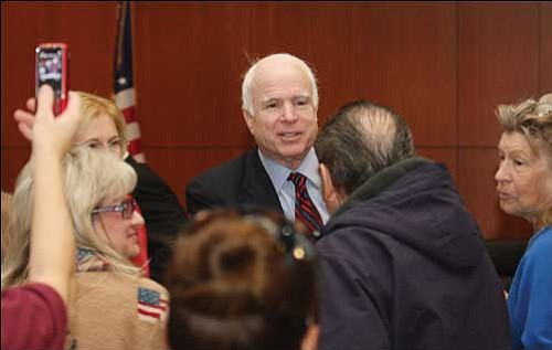 In this 2009 file photo, Arizona Sen. John McCain shakes hands with local residents at the Mohave  County Administration Building .