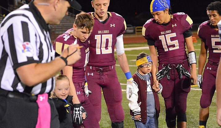 Winslow football team and children with Down Syndrome participate in the traditional coin toss before the start of the Oct. 13 game against the Payson Longhorns.