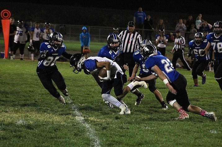 From left, Kingman Academy's Jacob Kidd (86), Stevie Wusstig (2), Tyler Wheeler (9) and Joey Martin (22) attempt to bring down a Paradise Honors running back last Friday. The Tigers finish the regular season tonight with a home game against Arete Prep.