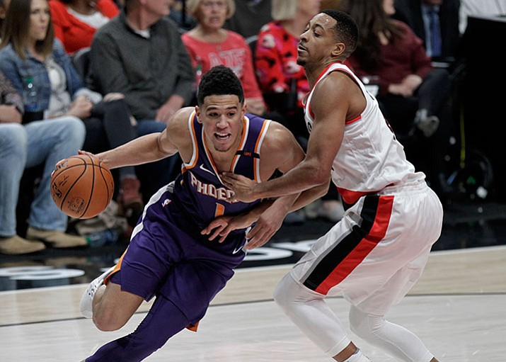 Suns guard Devin Booker, left, drives to the basket as Portland Trail Blazers guard CJ McCollum defends during the first half of an NBA basketball game in Portland, Ore., Saturday, Oct. 28, 2017. (Steve Dipaola/AP)
