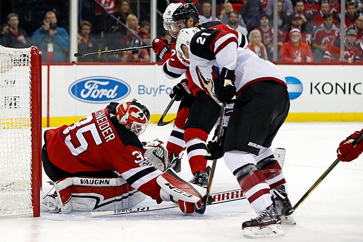 New Jersey Devils goalie Cory Schneider makes a save on a shot by Arizona Coyotes' Derek Stepan (21) during the third period of an NHL hockey game, Saturday, Oct. 28, 2017, in Newark, N.J. The Devils won 4-3. (AP Photo/Adam Hunger)