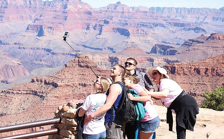 Close to 5 million tourists, like these, visited the Grand Canyon National Park last year. The National Park Service wants to double entry fees during peak season at the park, along with 16 others, to raise money for much-needed maintenance projects.