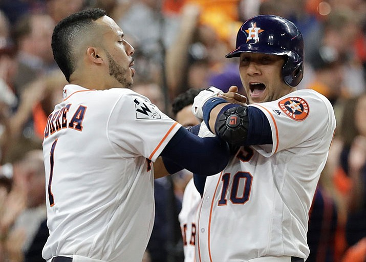 Houston Astros' Yuli Gurriel is congratulated by Carlos Correa after hitting a home run during the first inning of Game 3 of baseball's World Series against the Los Angeles Dodgers Friday, Oct. 27, 2017, in Houston. (AP Photo/David J. Phillip)