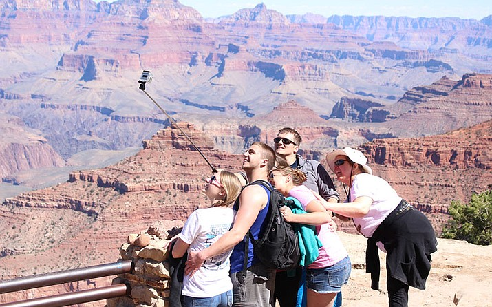 Close to 5 million tourists, like these, visited the Grand Canyon National Park last year. The National Park Service wants to double entry fees during peak season at the park, along with 16 others, to raise money for much-needed maintenance projects. (Photo by Sophia Kunthara/Cronkite News)