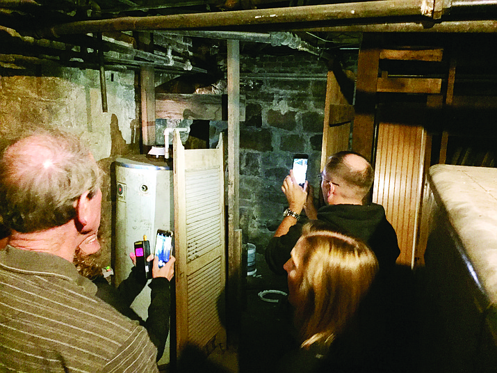 "Local ghost investigator Maureen Riley (center-short hair head turned) leads a group who are taking images of ""orbs"" and using a meter to detect presence of ghostly spirits in the off-limit basement areas of The Palace Restaurant and Saloon on Whiskey Row. (Kevin Hutson/Courtesy)"