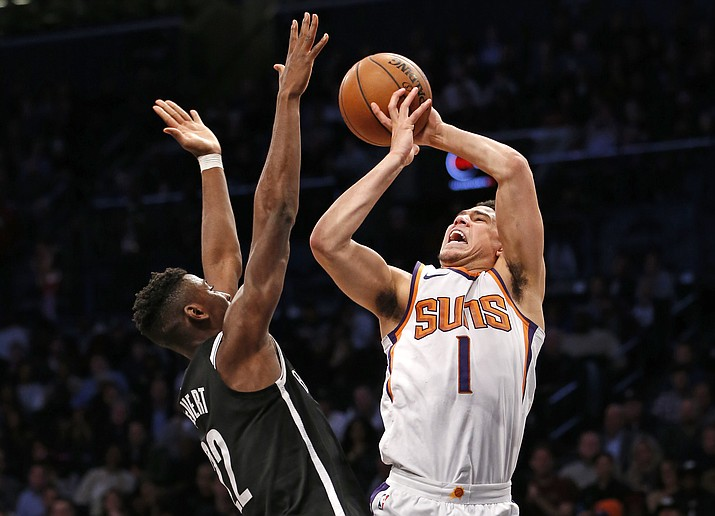 Brooklyn Nets guard Caris LeVert (22) defends Phoenix Suns guard Devin Booker (1) who loses control of the ball while shooting for two points in the second half of an NBA basketball game, Tuesday, Oct. 31, in New York. (Kathy Willens/AP)