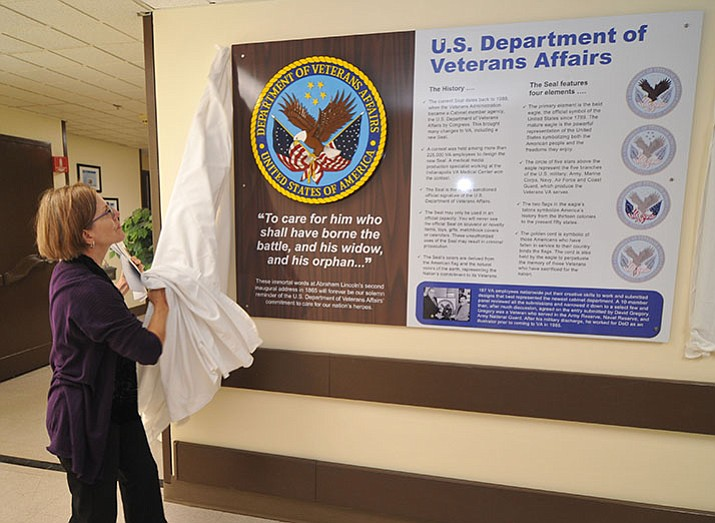 Medical Center Director Barbara Oemcke unveils the first panel during the unveiling ceremony of the VA Hospital History Wall Monday in the main hospital building in Prescott. (Les Stukenberg/Courier)