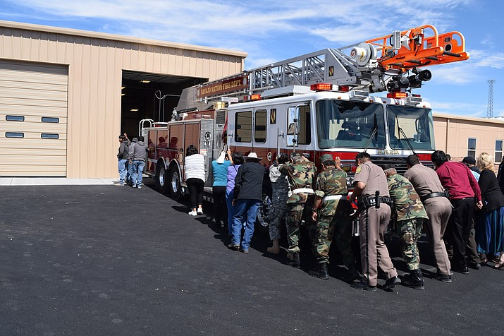 In a long held tradition, public officials, first responders and those who helped to construct and open the safety building help push the complex's first fire truck into the new Twin Arrows Public Safety Building. Submitted photo