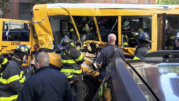 Emergency personnel work on a school bus after a driver rammed into it in New York. The head of the New York City schools system says two staff members and two students were injured in the bus that was struck by a motorist who drove a rented truck onto a bike path, killing eight people. (Sebastian Sobczak/BeautifulGoal.Org via AP)