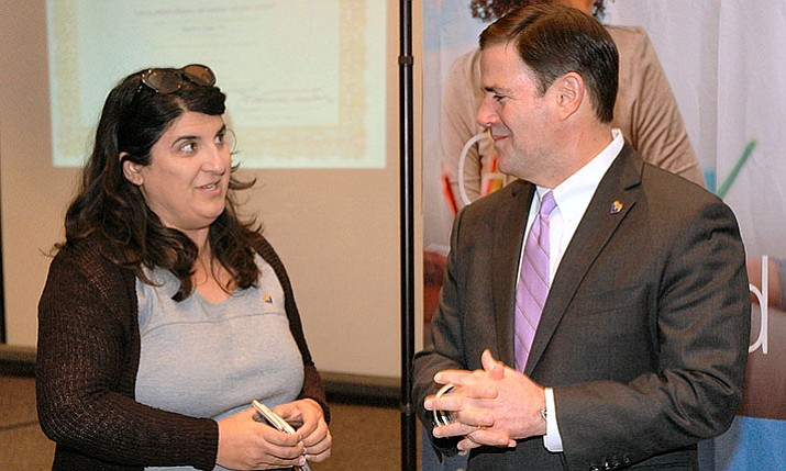 Gov. Doug Ducey (right) chats with Dawn Wallace, his education adviser, Thursday ahead of unveiling a plan to provide dollars in his budget to help ensure that students with vision and hearing impairment get help with reading skills. (Howard Fischer/Capitol Media Services)