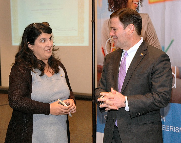 Gov. Doug Ducey chats with Dawn Wallace, his education advisor, Thursday ahead of unveiling a plan to provide dollars in his budget to help ensure that students with vision and hearing impairment get help with reading skills.