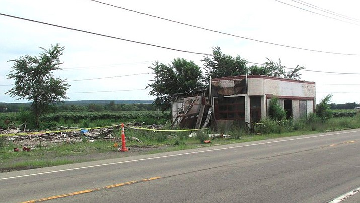 Authorities say Louis Delmonte, a western New York town official, has been cited for trying to bury his defunct auto repair garage in a large hole. (Department of Environmental Conservation)