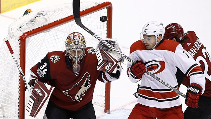 Carolina Hurricanes center Derek Ryan (7) tries to redirect the puck in front of Arizona Coyotes goalie Antti Raanta (32) as Coyotes' Oliver Ekman-Larsson, right, defends during the third period of an NHL hockey game Saturday, Nov. 4, 2017, in Glendale, Ariz. The Coyotes defeated the Hurricanes 2-1 in a shootout.