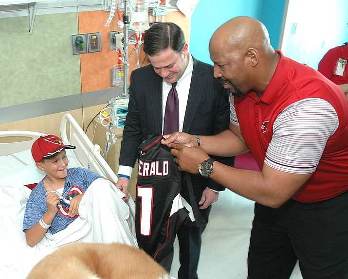 "Gov. Doug Ducey and former Cardinals player Michael Bankson visit with Seth Espinoza at Phoenix Children's Hospital Tuesday. The governor wants to use state funds to keep a children's health insurance program alive following congressional inaction. Ducey wrote, ""KidsCare can fairly be described as a work support program that provides healthcare coverage for children of low-income, working parents who don't make enough to pay for commercial coverage."" (Capitol Media Services photo by Howard Fischer)"