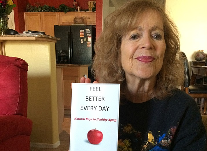 Carol in her home with her book. (Nanci Hutson/Courier)