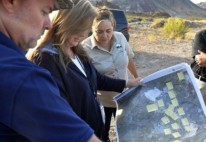 Mohave County Assessor Jeanne Kentch (tan shirt), Kingman Assessor Supervisor Dennis Wheeler, and Sixberry look over a map listing properties that were to be canvassed in Oatman.