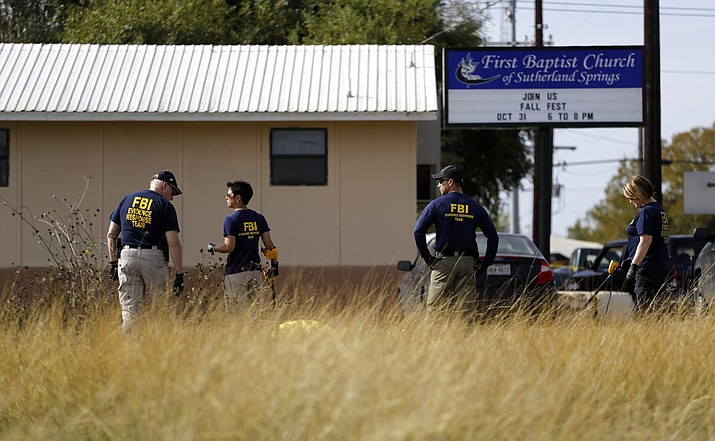 Law enforcement officials investigate the scene of a shooting at the First Baptist Church of Sutherland Springs, Monday, Nov. 6, 2017, in Sutherland Springs, Texas. A man opened fire inside the church in the small South Texas community on Sunday, killing and wounding many. (AP Photo/Eric Gay)