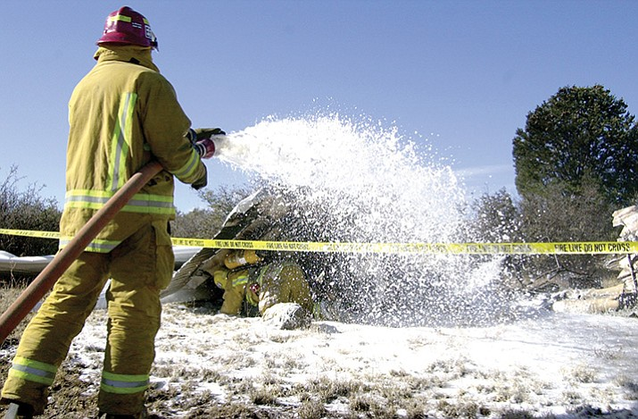 Firefighters work the site of a fatal plane crash in 2001. Two people died in the crash near Prescott's airport. (Les Stukenberg/Courier file)