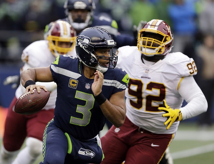 In this Sunday, Nov. 5, 2017, file photo, Seattle Seahawks quarterback Russell Wilson (3) scrambles away from Washington Redskins defensive end Stacy McGee (92) in the second half of an NFL football game in Seattle. The Seahawks are favored again when they face the Arizona Cardinals on Thursday night. (Stephen Brashear/AP, File)