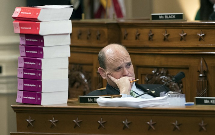 Rep. Tom Reed, R-N.Y., listens as he sits next to a stack of IRS Code volumes as the House Ways and Means Committee begins the markup process of the GOP's far-reaching tax overhaul Monday, Nov. 6, 2017, on Capitol Hill in Washington. (J. Scott Applewhite/AP)