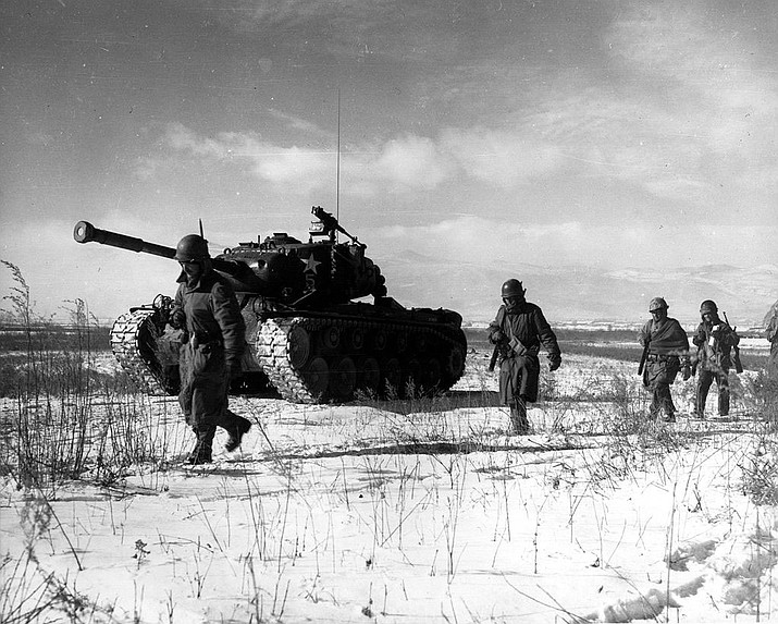 A column of troops and armor of the 1st Marine Division move through communist Chinese lines during their successful breakout from the Chosin Reservoir in North Korea. The Marines were besieged when the Chinese entered the Korean War on Nov. 27, 1950 by sending 200,000 shock troops against Allied forces.