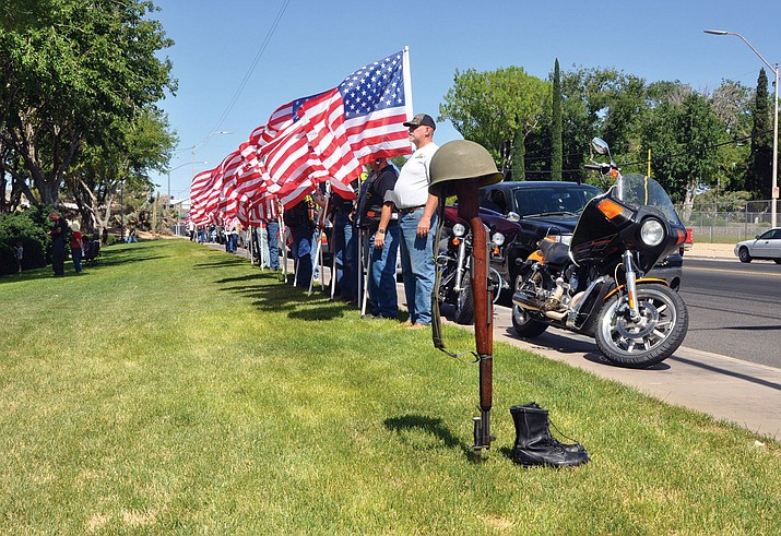 A silent tribute of an M-1 rifle, helmet and boots representing a fallen soldier stands adjacent to Kingman Veterans Memorial Park at Locomotive Park as members of the Mohave County Patriot Guard Riders stand holding American flags at a previous ceremony.