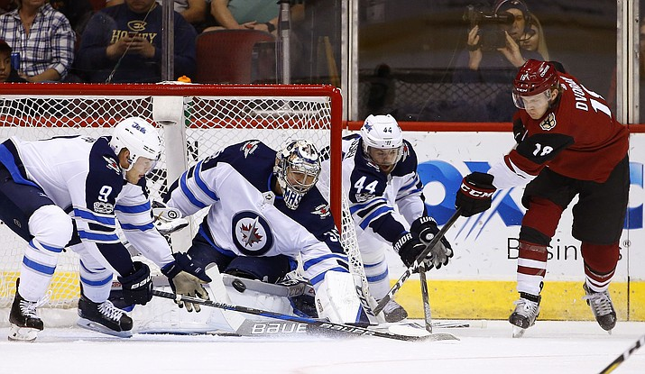 Arizona Coyotes center Christian Dvorak (18) gets his shot stopped by Winnipeg Jets center Andrew Copp (9), goalie Steve Mason (35) and defenseman Josh Morrissey (44) during the first period of an NHL hockey game Saturday, Nov. 11,  in Glendale. (Ross D. Franklin/AP)