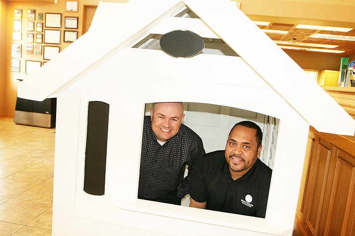 Country Bank Cottonwood Branch Manager Mark Tufte, left, and Benchmark Builders owner Rodney Vincent show off one of the two playhouses their businesses will raffle off to raise money for the Wounded Warriors Project and for Habitat for Humanity. The raffle will be held on Dec. 23. (Photo by Bill Helm)
