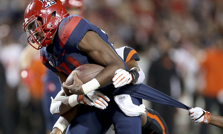 Arizona quarterback Khalil Tate (14) drags a couple of Oregon State defenders into the end zone on a touchdown run during the second quarter of an NCAA college football game Saturday, Nov. 11, 2017, Tucson, Ariz. (Kelly Presnell/Arizona Daily Star via AP)