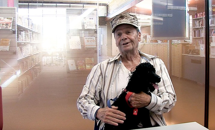 Rich Libertini, an 82-year-old veteran, sits for an interview at Mohave Community College. With his pal Atlas at his side, Libertini expects to graduate with an associate's degree next year.