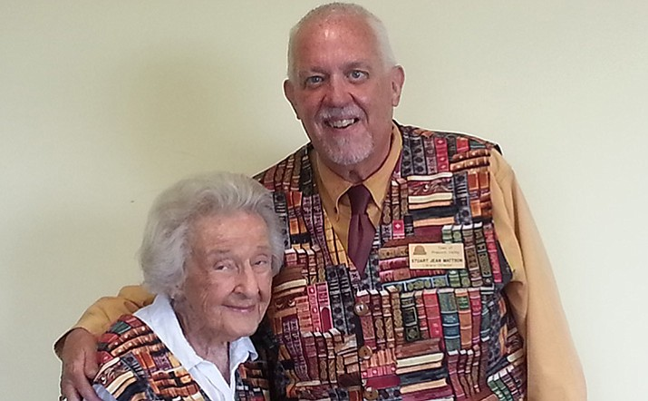 "Stuart Mattson: A picture of him wearing a vest he had crafted from ""book"" material he found. He is standing with long-time patron and friend, Elisabeth Ruffner of Prescott, who is wearing a matching vest from the same material. Mattson will retire on Jan. 2 after 30 years at the Prescott Valley Library. (Courtesy)"