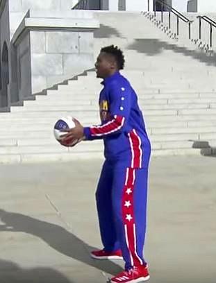 Harlem Globetrotter Thunder Law prepares to sink a basket on a 50-foot high hoop.
