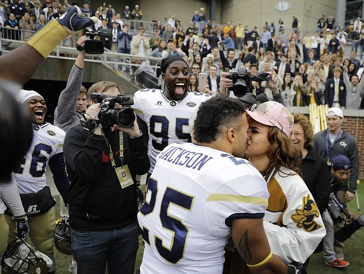 Georgia Tech's Tre' Jackson proposes to his girlfriend Desi Nathe in front of teammates and spectators after Georgia Tech beat Virginia Tech 28-22 in an NCAA college football game in Atlanta, Saturday, Nov. 11, 2017. (AP Photo/David Goldman)