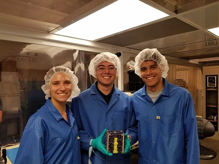 Members of the Embry-Riddle Aeronautical University EagleSat team pose with the cube satellite they designed. From left are Deborah Jackson, EagleSat-1 project manager; Sean Akana, systems lead; and Delbert Conn III, previous project manager. (Embry-Riddle Aeronautical University/Courtesy)