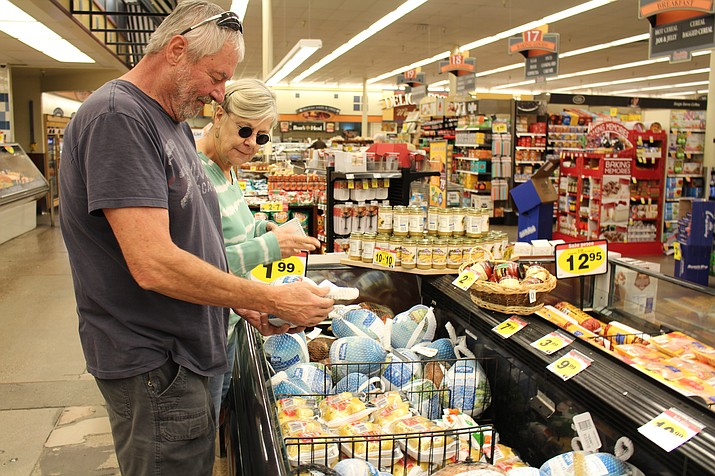 Mack and Gloria McClellan look over turkey breasts and cornish hens at Smith's grocery store in Kingman. The store will be a madhouse in the days before Thanksgiving.