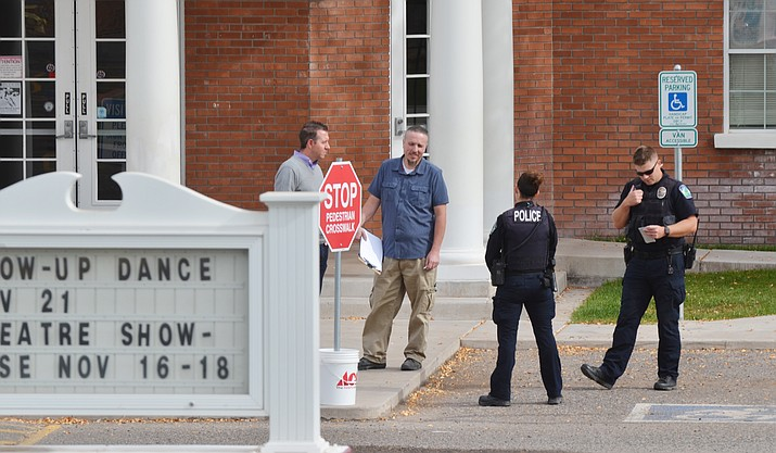 Police confer with officials at American Heritage Academy Wednesday after police dispatch received a call from a mother who said her daughter had texted her about a gunman at the school. American Heritage was having a lockdown drill at the time the call was made to police. VVN/Vyto Starinskas
