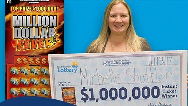 Michelle Shuffler holds a check for $1 million. Shuffler first won $10,000 on one scratch-off ticket before deciding to buy another ticket 22 miles away on the same day. She claimed both prizes Monday. (North Carolina Education Lottery/Distributed Photo)