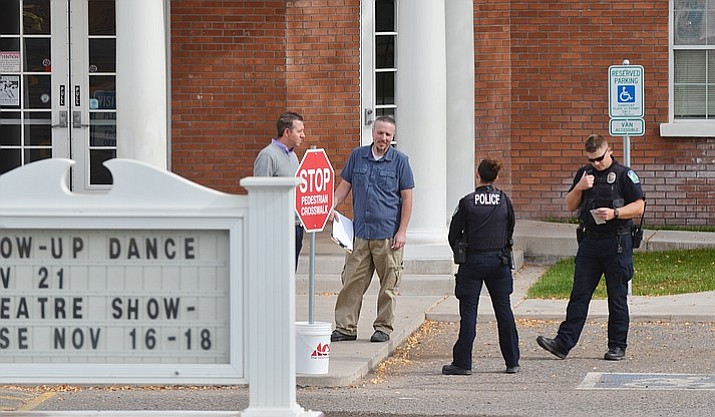 Police confer with officials at American Heritage Academy Wednesday after police dispatch received a call from a mother who said her daughter had texted her about a gunman at the school. American Heritage was having a lockdown drill at the time the call was made to police. (VVN/Vyto Starinskas)