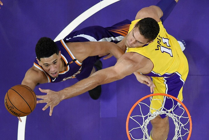 Phoenix Suns guard Devin Booker, left, shoots as Los Angeles Lakers center Brook Lopez defends during the first half of an NBA basketball game, Friday, Nov. 17, 2017, in Los Angeles. (Mark J. Terrill/AP)