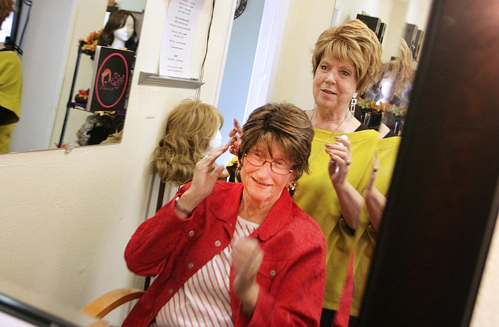 Linda Jo Safford of Jazzy Gal's Wigs and More helps Jan Osterhout try on a wig. (Photo by Bill Helm)