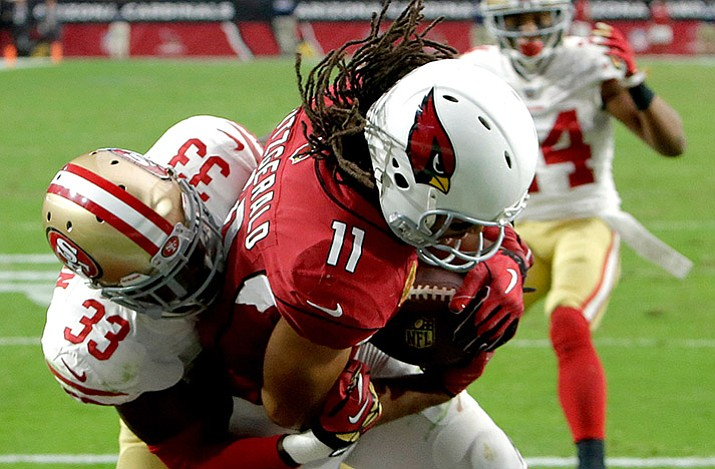 Arizona Cardinals wide receiver Larry Fitzgerald (11) pulls in the game winning touchdown Oct. 1, 2017, as San Francisco 49ers cornerback Rashard Robinson (33) defends during overtime of an NFL football gamevin Glendale. At age 34, Fitzgerald is tied for second in the NFL in receptions this season with 60, one fewer than Jarvis Landry. He's caught a pass in 204 consecutive games. (Rick Scuteri/AP, File)