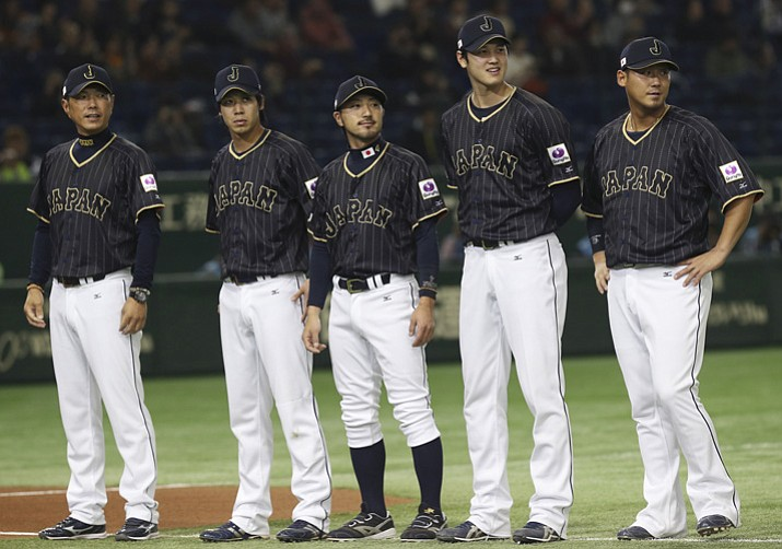 This Nov. 11, 2016, file photo shows Team Japan, from left, manager Hiroki Kokubo, infielder Tetsuto Yamada, infielder Ryosuke Kikuchi and designated hitter Shohei Ohtani and infielder Sho Nakata standing during a ceremony prior to their international exhibition series baseball game against Mexico at Tokyo Dome in Tokyo. A person familiar with the agreement tells The Associated Press that Major League Baseball, its Japanese counterpart and the American players' union agreed Tuesday, Nov. 21, 2017,  to a new posting system that could allow Japanese star pitcher-outfielder Shohei Ohtani to be put up for bid next week. (Koji Sasahara/AP, File)