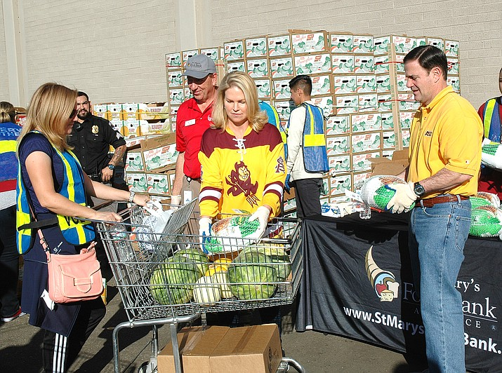 Arizona Gov. Doug Ducey (right) helps out at a food bank before Thanksgiving. The governor said it's too soon to talk about a possible reelection campaign. (Howard Fischer/Capitol Media Services)