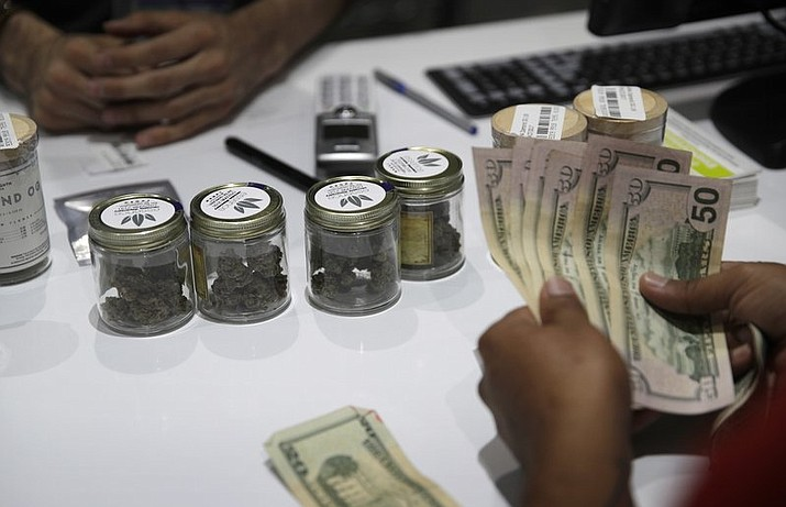 In this July 1, 2017 file photo, a person buys marijuana at the Essence cannabis dispensary in Las Vegas. The Las Vegas Sun reports more than 40 dispensaries in the Las Vegas area will offer Black Friday discounts on marijuana flower products, edibles such as chocolates, and concentrates. (AP Photo/John Locher, File)