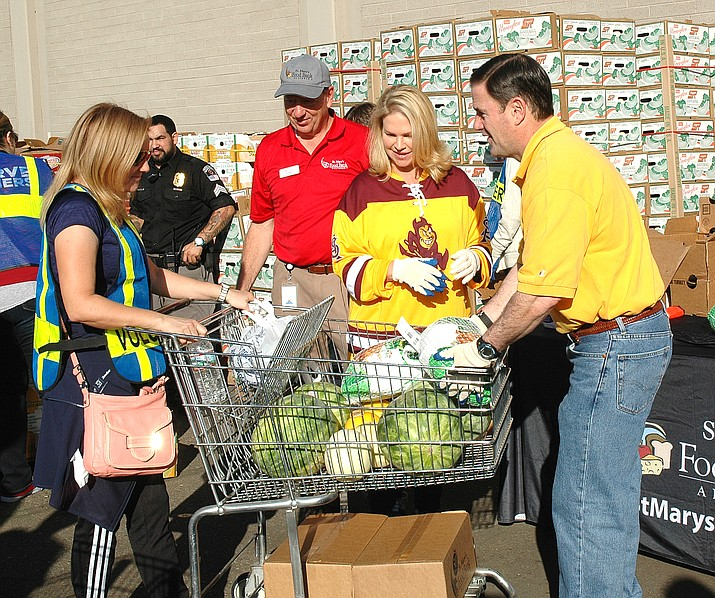 Gov. Doug Ducey and wife Angela, also wearing Arizona State University colos, help load turkeys into shopping carts Wednesday as part of the annual Thanksgiving food donation at St. Mary's Food Bank. Those carts eventually are wheeled to waiting vehicles. (Capitol Media Services photo by Howard Fischer)