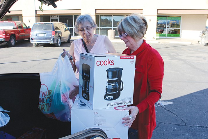 Linda Hutchinson, right, of JC Penney helps customer Connie Czymbor load merchandise into her car on Black Friday. Czymbor said she also shops online for Christmas gifts, like the karaoke machine she bought for her husband from Walmart.