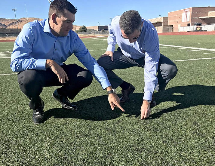 School Superintendent Dan Streeter, left, points out the rubber pellets that are exposed in the worn areas of turf on the Bradshaw Mountain High School football field. The district is looking at replacing the synthetic turf on the baseball and football fields. (Sue Tone/Tribune)