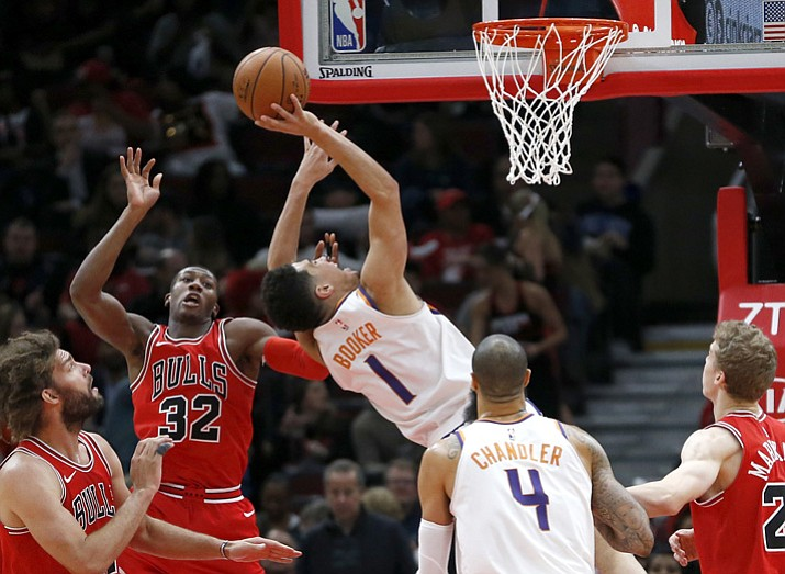 Phoenix Suns' Devin Booker (1) drives to the basket past Chicago Bulls' Kris Dunn (32) as Lauri Markkanen (24) Tyson Chandler (4) and Robin Lopez watch during the first half of an NBA basketball game Tuesday, Nov. 28, 2017, in Chicago. (Charles Rex Arbogast/AP)