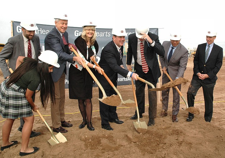 Gov. Doug Ducey, center, helps break ground Wednesday for a new branch of GreatHearts Academy, a nonprofit charter school network. The campus is being financed with public help because of legislation pushed by the governor to have the state guarantee payment on its borrowing.