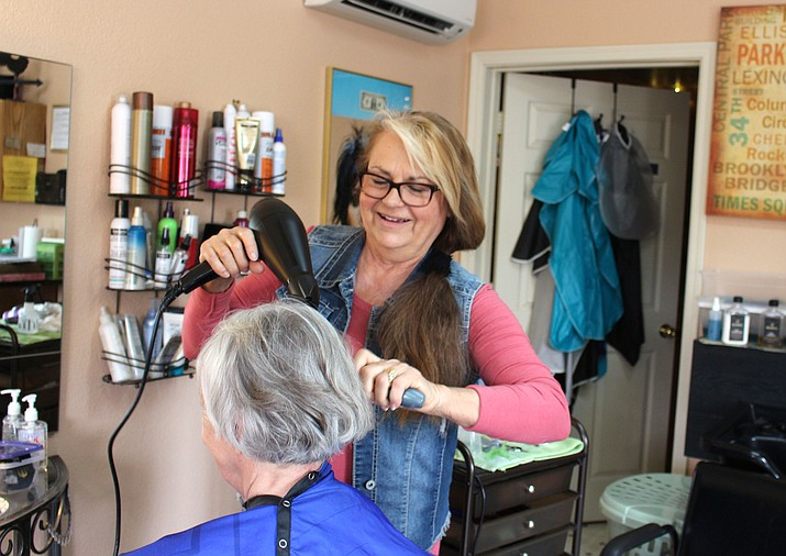 Debbie Foresta, owner of Grand Central Salon, styles a customer's hair Wednesday. She said there's more to getting a state cosmetology license than learning how to cut hair.